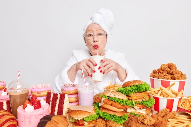Piękna starsza kobieta pije napój gazowany zjada żywność o wysokiej zawartości tłuszczu i cukru, ma niezdrową, niezrównoważoną rację żywieniową
