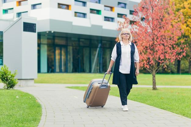 Piękna starsza kobieta podróżuje z dużą walizką podróżną, na tle pięknego nowoczesnego budynku
