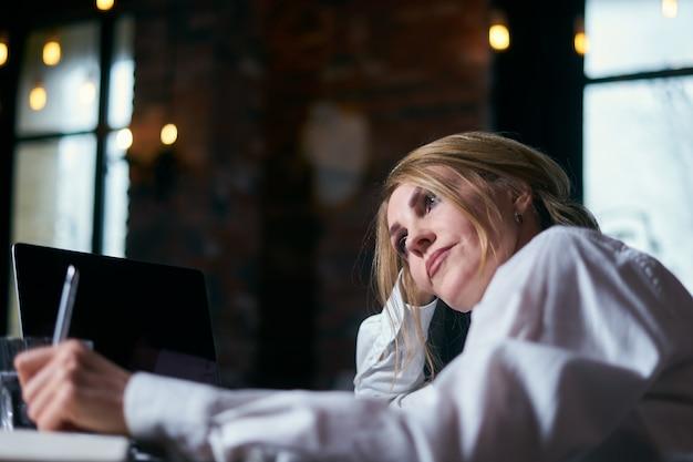 Piękna starsza kobieta pracuje w kawiarni z laptopem i pisze w notepad