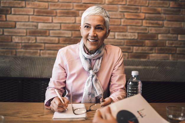 Piękna starsza kobieta przeprowadza rozmowę kwalifikacyjną.