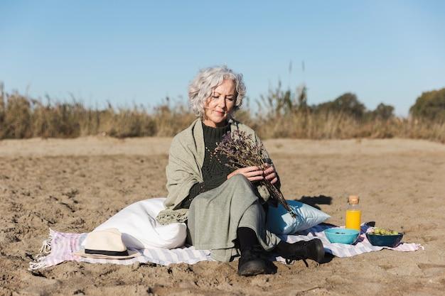 Piękna starsza kobieta relaksuje outdoors