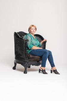 Piękna starsza kobieta siedzi na fotelu przed białym tłem
