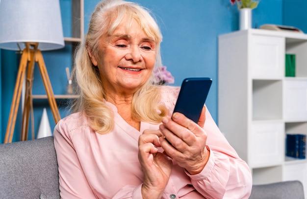 Piękna starsza kobieta siedzi sama w domu i łączy się z internetem za pomocą urządzenia typu smartphone