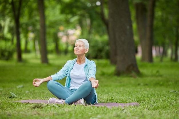 Piękna starsza kobieta spędza letni poranek siedząc na macie w parku medytując z zamkniętymi oczami