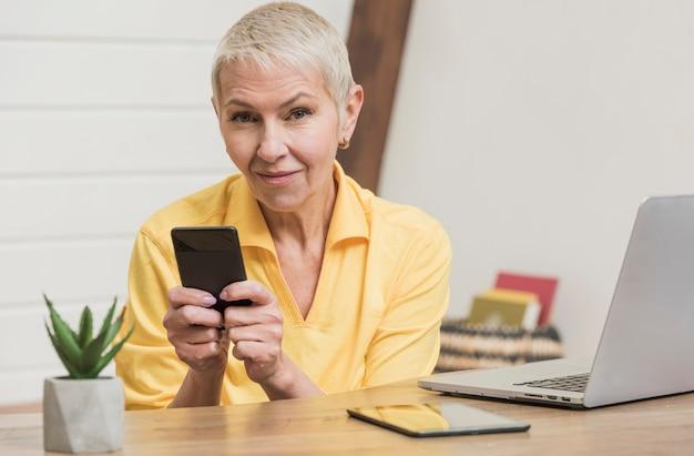 Piękna starsza kobieta używa telefon