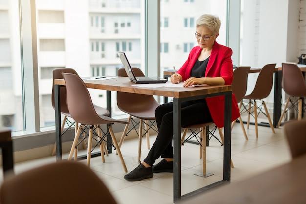 Piękna starsza kobieta w czerwonej kurtce pracuje w biurze z laptopem