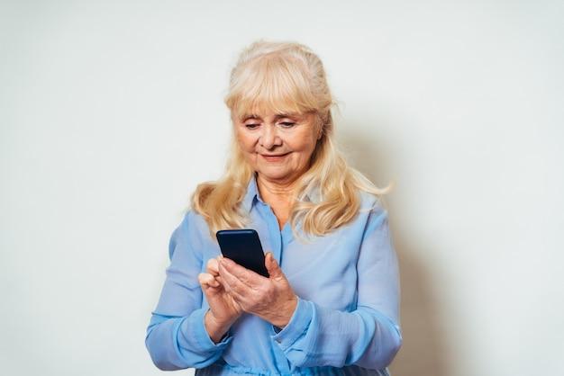 Piękna starsza kobieta w domu i patrząc na przód uśmiechnięta całkiem dorosły ponad 60 lat