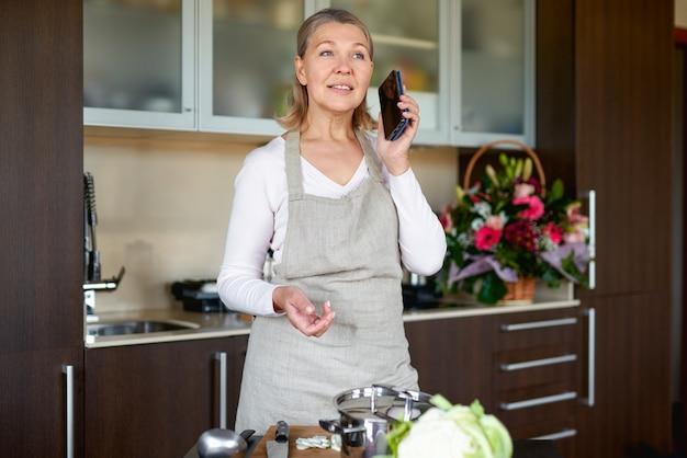 Piękna starsza kobieta w fartuchu w kuchni przygotowuje jedzenie i trzyma inteligentny telefon