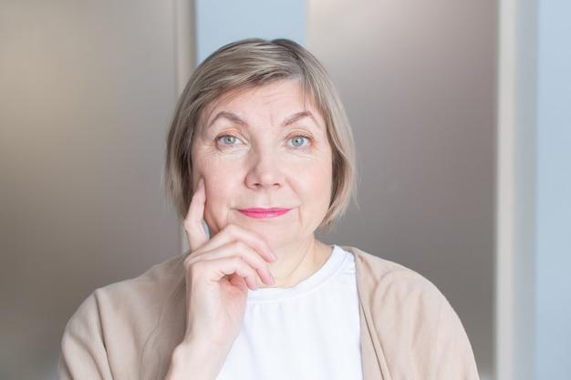 Piękna starsza kobieta z siwymi włosami, uśmiechając się, patrzy w kamerę
