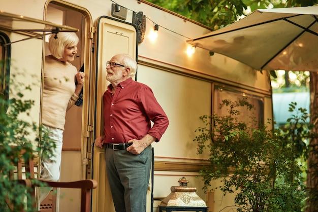 Piękna starsza pani rozmawiająca z mężem przy kamperze