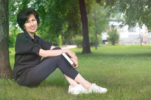 Piękna starsza starsza dorosła kobieta siedzi na ziemi, trawa w parku latem, czytając ciekawą książkę wsparty na drzewie