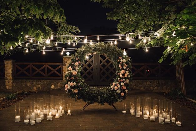 Piękna strefa fotograficzna z dużym wieńcem ozdobionym zielenią i różami na środku, świecami po bokach i girlandą zawieszoną między drzewami