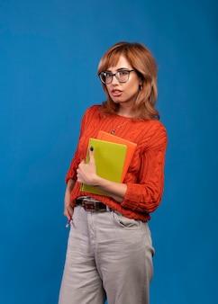 Piękna studencka kobieta z książkami. pojedynczo na niebiesko.