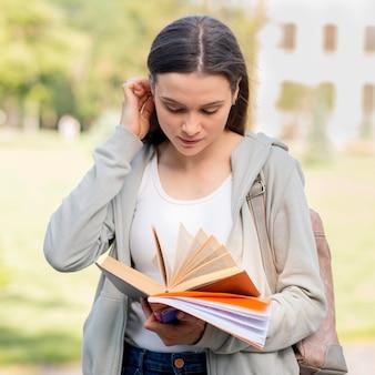 Piękna studencka przygotowywająca książka przy kampusem