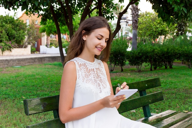 Piękna studentka pisze swoje pomysły i myśli do notebooka siedzącego na ławce w parku