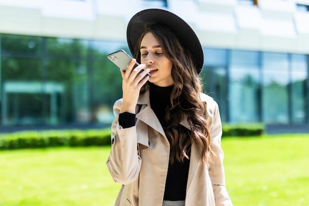 Piękna studentka rozmawia z systemem głośnomówiącym smartfona, trzymając folder na kampusie uniwersytetu.