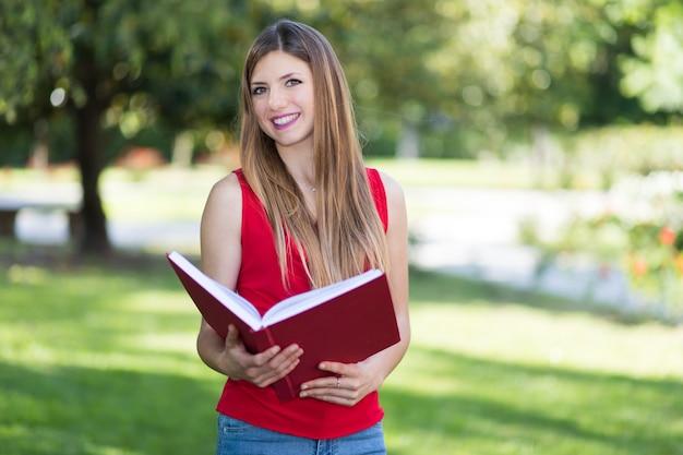 Piękna studentka trzyma książkę na świeżym powietrzu