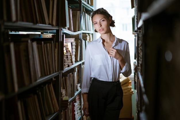 Piękna studentka w białej koszuli stoi między rzędami w bibliotece