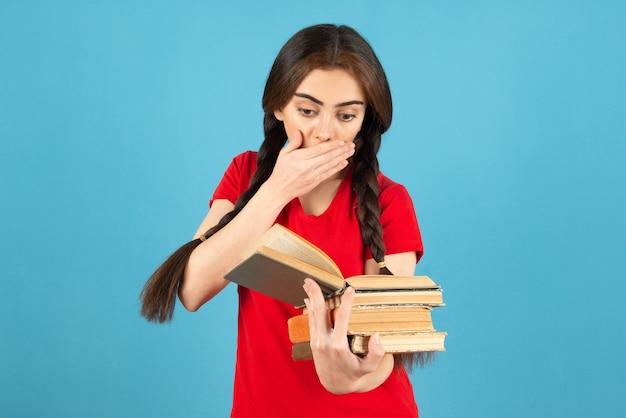 Piękna studentka w czerwonej koszulce czytanie książki z wyrazem szoku.
