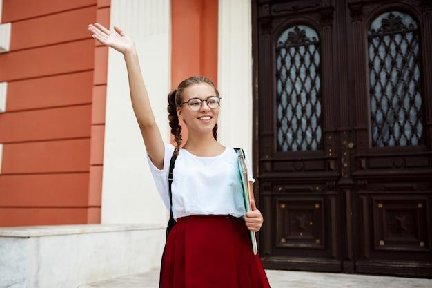 Piękna studentka w okularach, uśmiechając się, pozdrawiając, trzymając foldery na zewnątrz