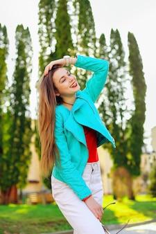 Piękna stylowa dziewczyna uśmiecha się i trzyma długie blond włosy