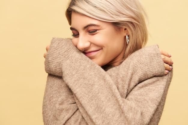 Piękna stylowa dziewczyna z piercingiem twarzy jest w dobrym nastroju, pozuje odizolowana z rękami skrzyżowanymi na piersi, ubrana w przytulny kaszmirowy sweter z długimi rękawami, rozgrzewa się w zimny grudniowy dzień