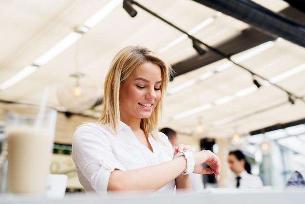 Piękna stylowa dziewczyna za pomocą nowoczesnego zegarka w kawiarni.