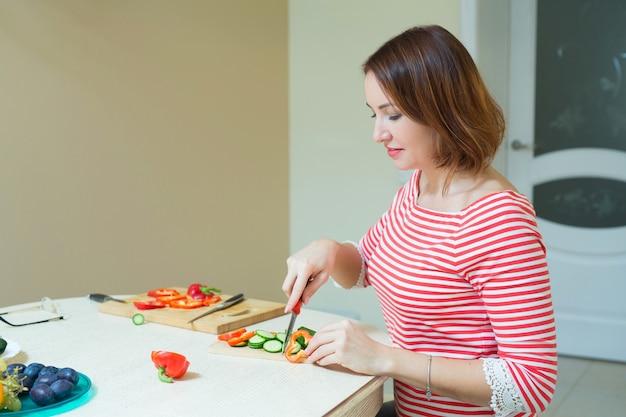 Piękna stylowa kobieta cięcia sałatki w kuchni