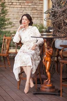 Piękna stylowa kobieta w beżowej sukience siedzi w kawiarni na świeżym powietrzu. portret szczęśliwa kobieta w kawiarni na świeżym powietrzu