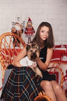 Piękna stylowa kobieta w czarnej sukni trzyma psa