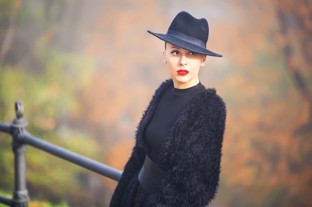 Piękna stylowa kobieta w czarnym kapeluszu w jesień parku