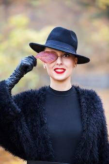 Piękna stylowa kobieta w czarnym kapeluszu z liści jesienią