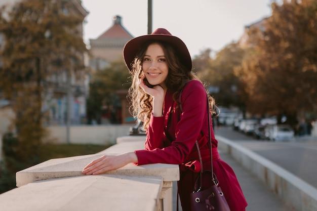 Piękna stylowa kobieta w fioletowym garniturze spaceru ulicą miasta, trend w modzie wiosna lato jesień sezon w kapeluszu, trzymając torebkę
