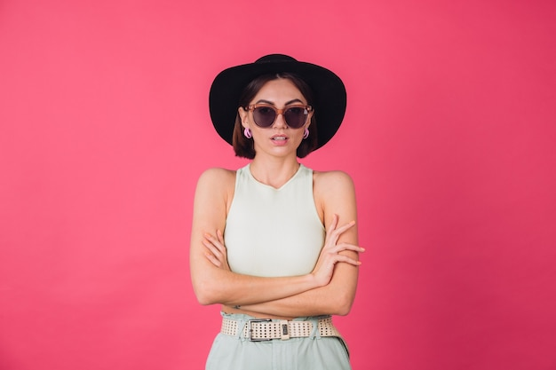 Piękna stylowa kobieta w kapeluszu i okularach przeciwsłonecznych, pozowanie na różowej czerwonej ścianie