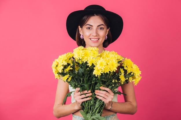 Piękna stylowa kobieta w kapeluszu pozowanie, trzymając duży bukiet żółtych astry, wiosenny nastrój, na białym tle pozytywne emocje