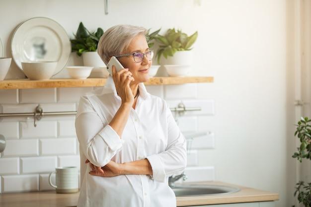 Piękna stylowa kobieta w wieku z telefonem komórkowym