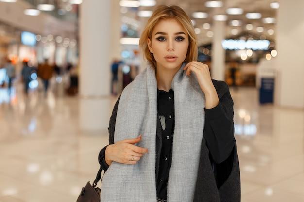 Piękna stylowa młoda blond kobieta w modnym szarym szaliku i płaszczu w centrum handlowym