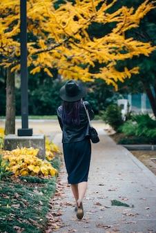 Piękna stylowa młoda dama spaceru w parku jesienią