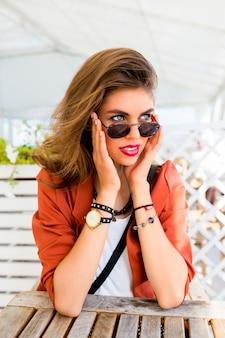 Piękna stylowa młoda dziewczyna przyjaźni siedzi w letniej restauracji i marzy. szczęśliwy słoneczny letni nastrój wakacji, jasne kolory. mają pełne czerwone usta i duże niebieskie oczy.