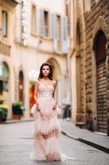 Piękna stylowa modelka w różowej sukni ślubnej sfotografowanej we florencji, trzymająca niezwykły bukiet, modelka panny młodej z bukietem w rękach, sesja zdjęciowa panny młodej we florencji.