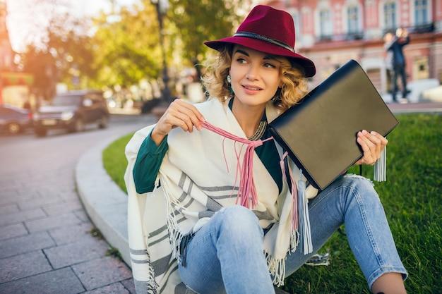 Piękna stylowa pani spacerująca po ulicy w pelerynie trzymając torebkę, akcesoria modowe, wiosenny trend w stylu ulicznym, uśmiechnięta