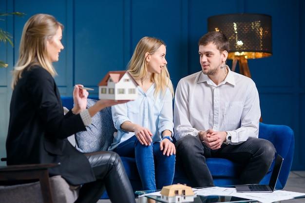 Piękna stylowa rodzina na spotkaniu z projektantem, pośrednik w obrocie nieruchomościami w stylowym niebieskim biurze.
