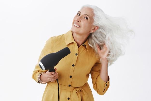 Piękna stylowa starsza kobieta za pomocą suszarki do włosów
