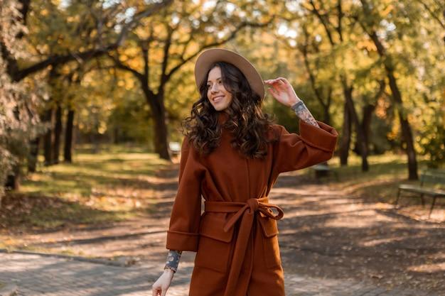 Piękna stylowa uśmiechnięta chuda kobieta z kręconymi włosami spacerująca po parku ubrana w ciepły brązowy płaszcz, jesień modny styl ulicy