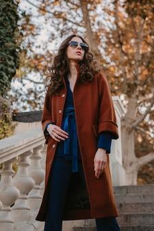 Piękna stylowa uśmiechnięta chuda kobieta z kręconymi włosami spacerująca po schodach ulicznych ubrana w ciepły brązowy płaszcz i niebieski garnitur, modny jesienny styl ulicy