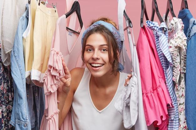 Piękna suczka o radosnym wyrazie, przeglądająca swoje ubrania, chętnie sama wybiera strój. uradowana kobieta przeglądająca garderobę, pozytywnie wyglądająca, pozująca w przymierzalni