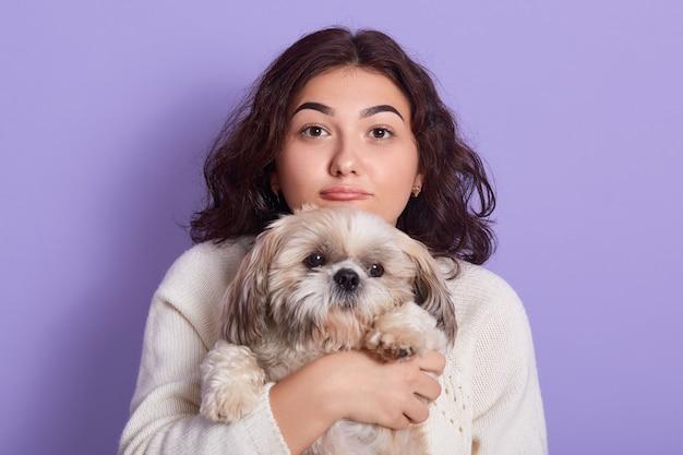 Piękna suczka trzyma pekińczyk, dba o zwierzę, ma wesoły nastrój, nosi biały sweter, modelki pozują odizolowane na fioletowej ścianie, suka z wydymanymi ustami.