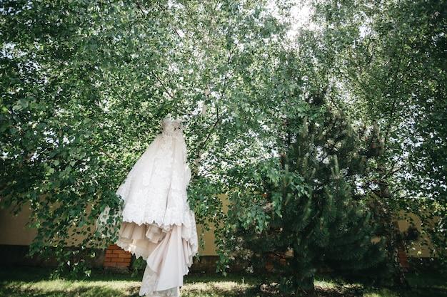 Piękna suknia panny młodej wisi wśród drzew