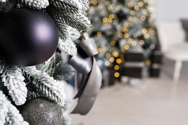 Piękna świąteczna gałąź choinki znajduje się w pokoju ozdobionym czarnymi bożonarodzeniowymi zabawkami, kulkami i kokardką