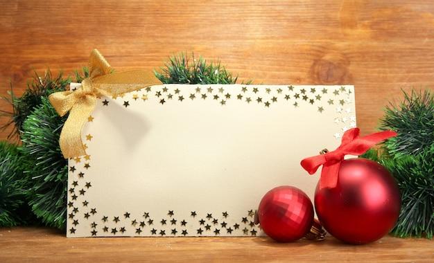 Piękna świąteczna kompozycja z pustą pocztówką na drewnianym tle